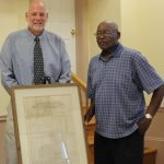 Dr. Darren Lisse (left) presents an 1841 edition of the Morning Star, an abolitionist newspaper, to James Taylor (right), president of the Jefferson County (W. Va.) Black History Preservation Society.